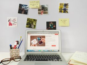 A monotonous work desk transformed into a personal corner, using square photo prints.